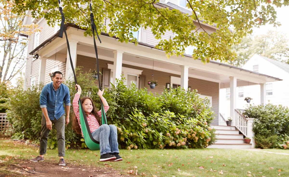 Dad pushing daughter on a swing in front of new house